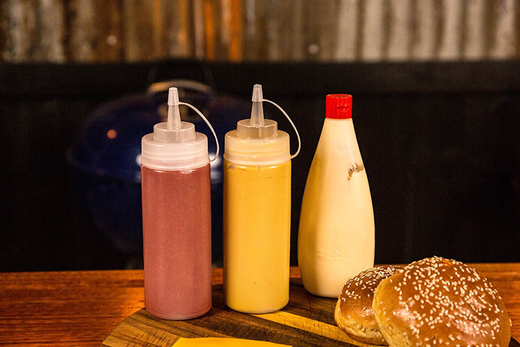 bottles with mustard, ketchup and mayonnaise on a wooden board