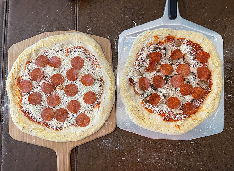 two uncooked pizzas on two pizza peels from Ooni
