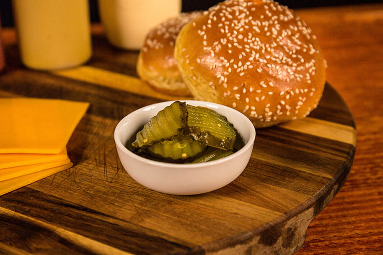 sliced pickles, cheese and burger buns on a wooden table