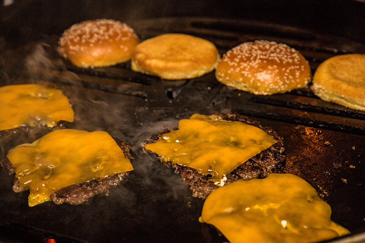 smash burger patties with cheese on a hotplate