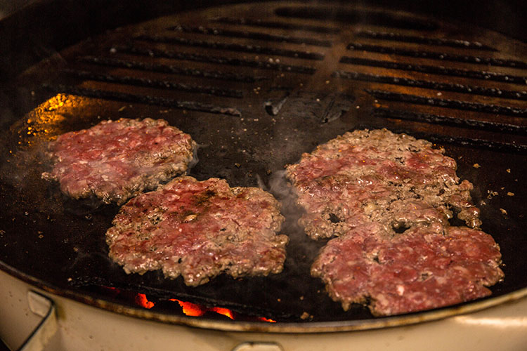 smashed burger patties on a weber kettle