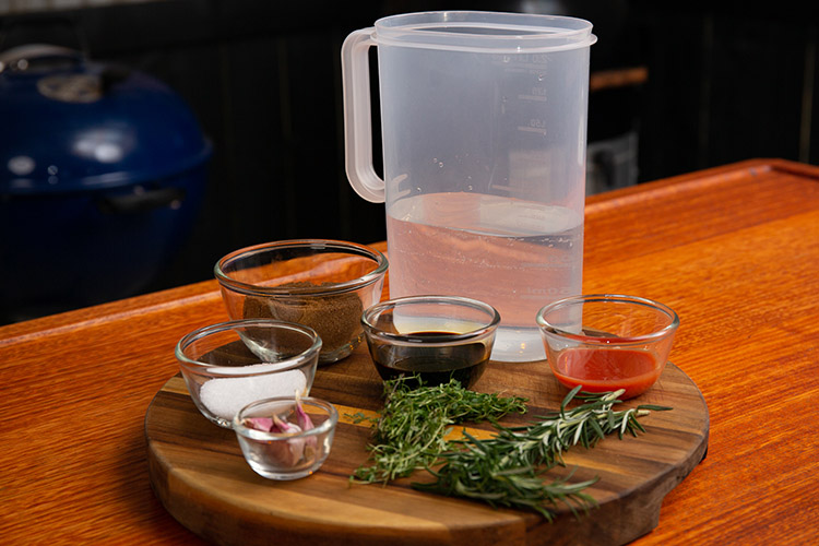 Chicken wing brine ingredients prepped in individual containers on a wooden tray
