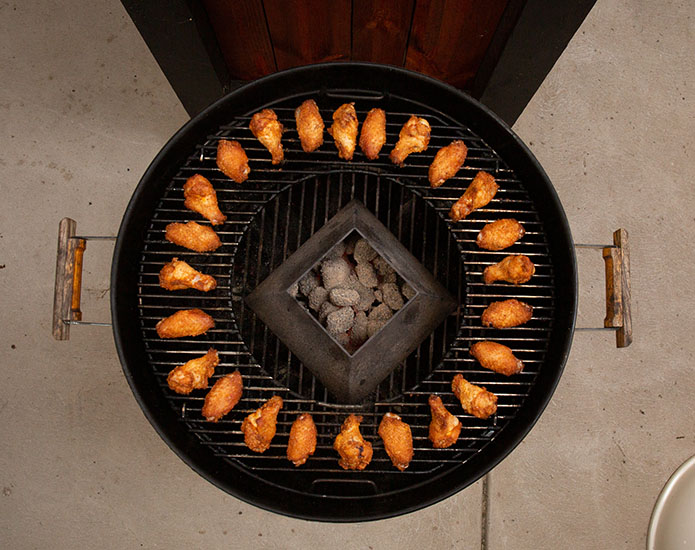 Chicken placed in a circle around the outside of the weber grill cooking