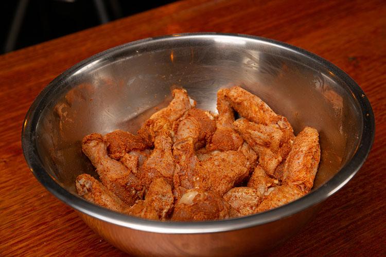 Seasoned raw chicken wings in a metal bowl