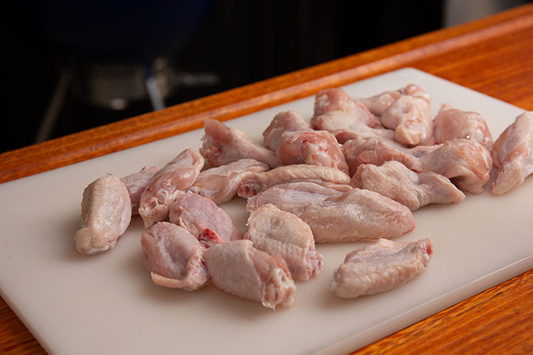 Prepped raw chicken wings on a white chopping board