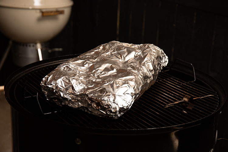 pork ribs covered in foil in a smoker