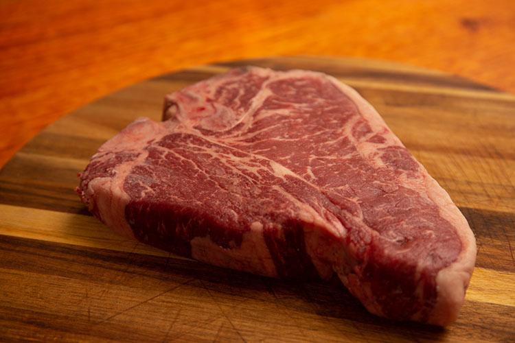 raw porterhouse steak on a wooden board