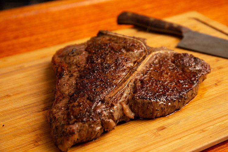 grilled porterhouse steak resting on a wooden board