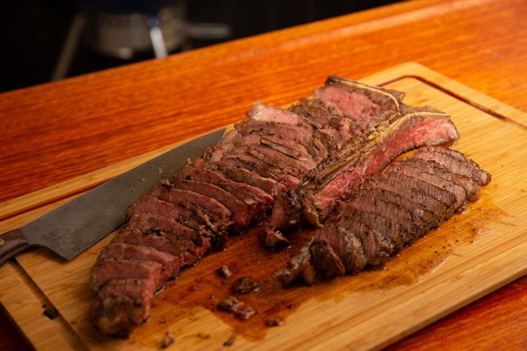 sliced porterhouse steak on a wooden board