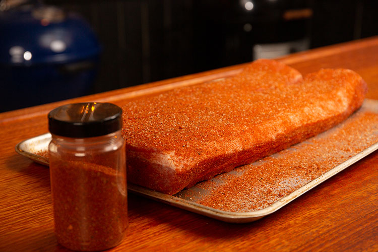 raw pork spare ribs seasoned with rub on a metal tray