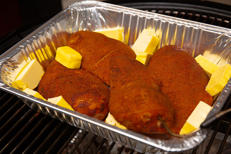 Smoked chicken breasts in a tin tray with cubes of butter