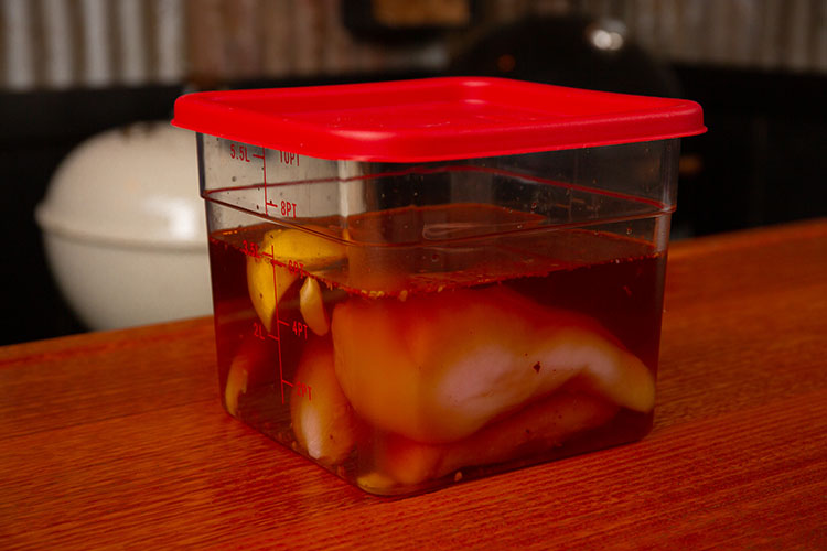 Chicken breast in a container with wet brine
