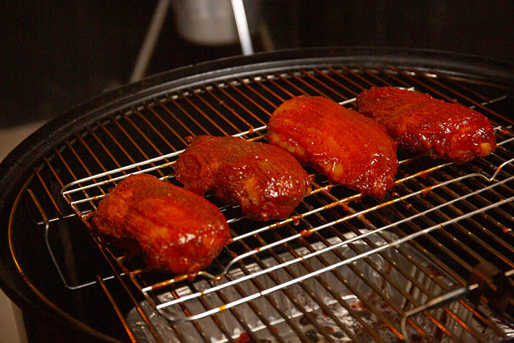 Glazed chicken breasts sitting on a wire rack in the smoker