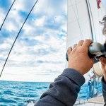 Person using binoculars on a yacht.