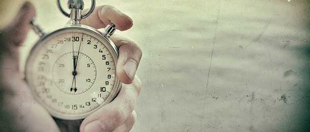 A hand holds a stopwatch.