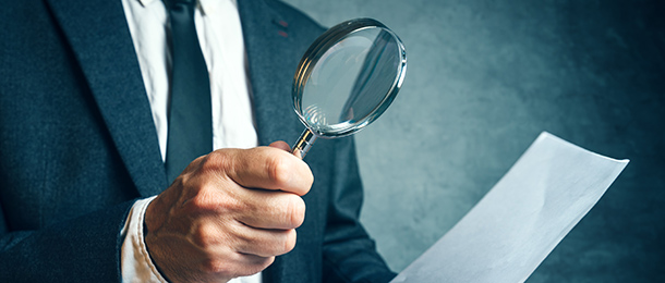 Man looks at a document through a magnifying glass