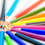 Sharp colorful pencils pointing toward each other.