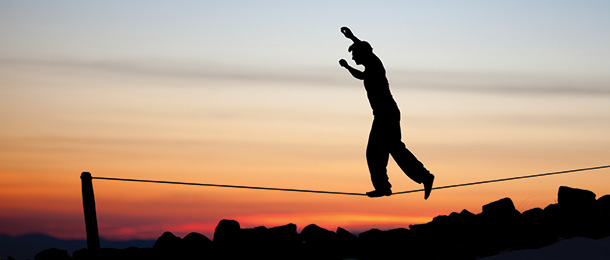 Person balances on a tightrope above the ground.