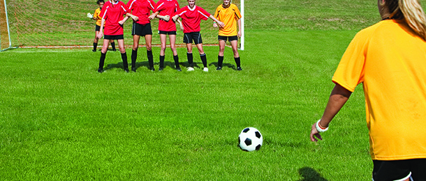 Female soccer player taking free kick