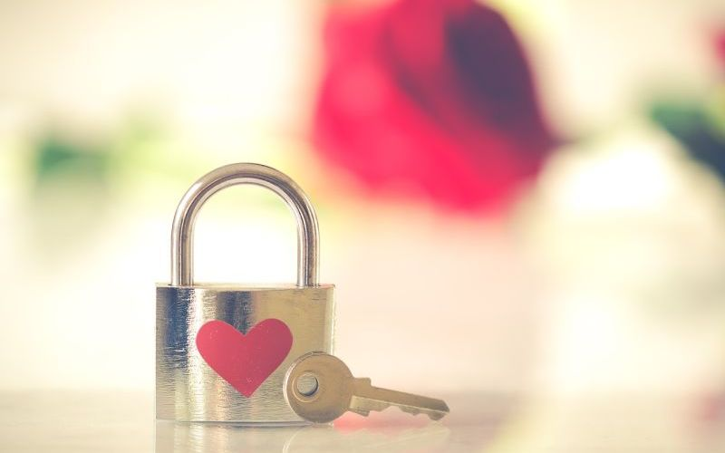 Image of a bronze colored padlock with a red heart on it.