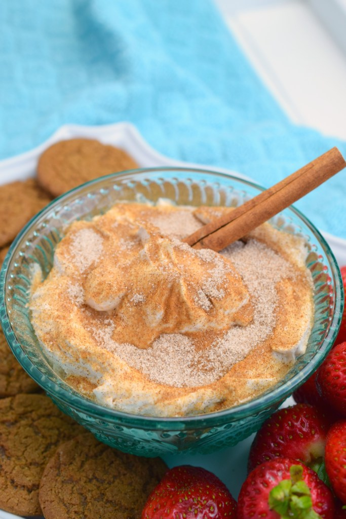 platter holding strawberries cookies and bowl of creamy churro dip with cinnamon stick in it