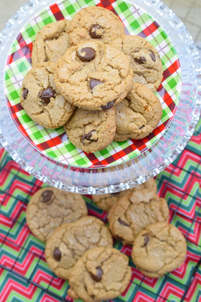 stacked plate holding cookies over wire rack with baked cookies and holiday fabric