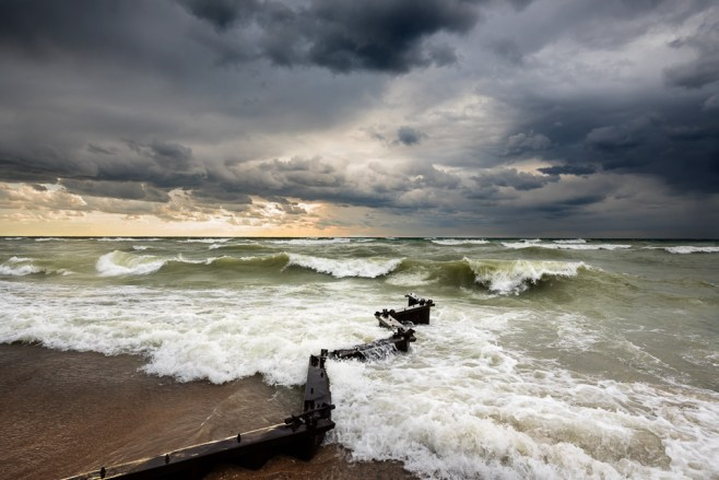 Moody skies and rolling waves crash around a breakwall at the Point Betsie Lighthouse on Lake Michigan