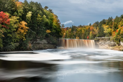 Michigan's Upper Peninsula's famous Tahquamenon Falls drops into the swirling waters below - surrounded by fall-colored trees