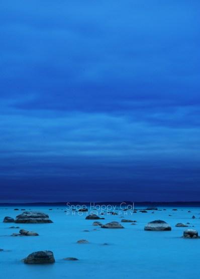 Photo: dark blue skies over light blue water