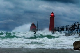 Photo: surfer on wild Lake Michigan waves, Grand Haven Lighthouse