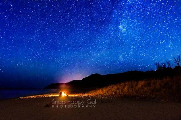 Photo: A couple enjoys a campfire under the stars at Esch Beach