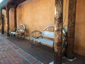 Unique benches along an adobe wall.