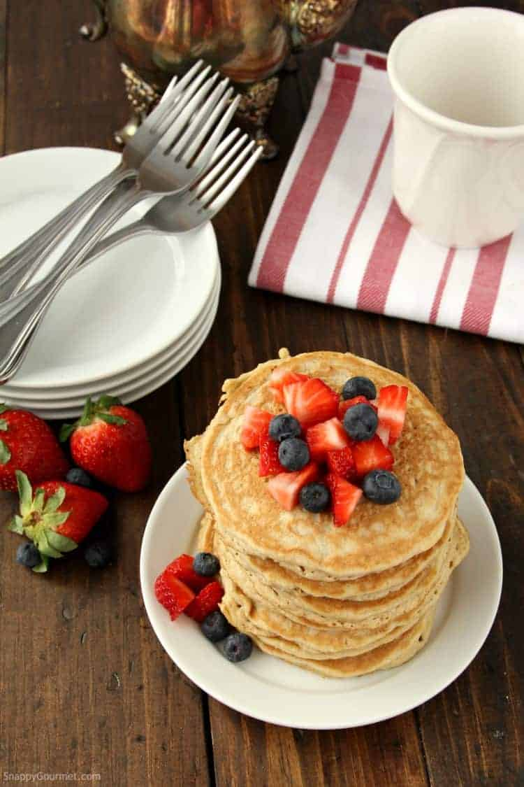 golden brown almond flour pancakes on plate with fruit