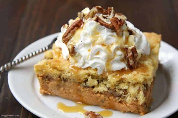 pumpkin dump cake on plate with caramel sauce, whipped cream, and pecans