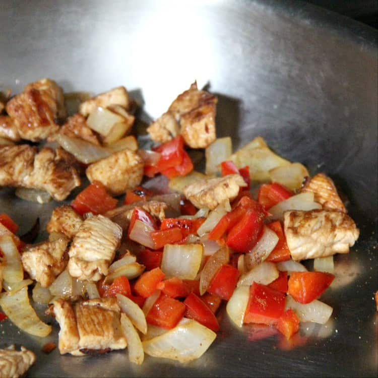 chicken, peppers, and onions in pan