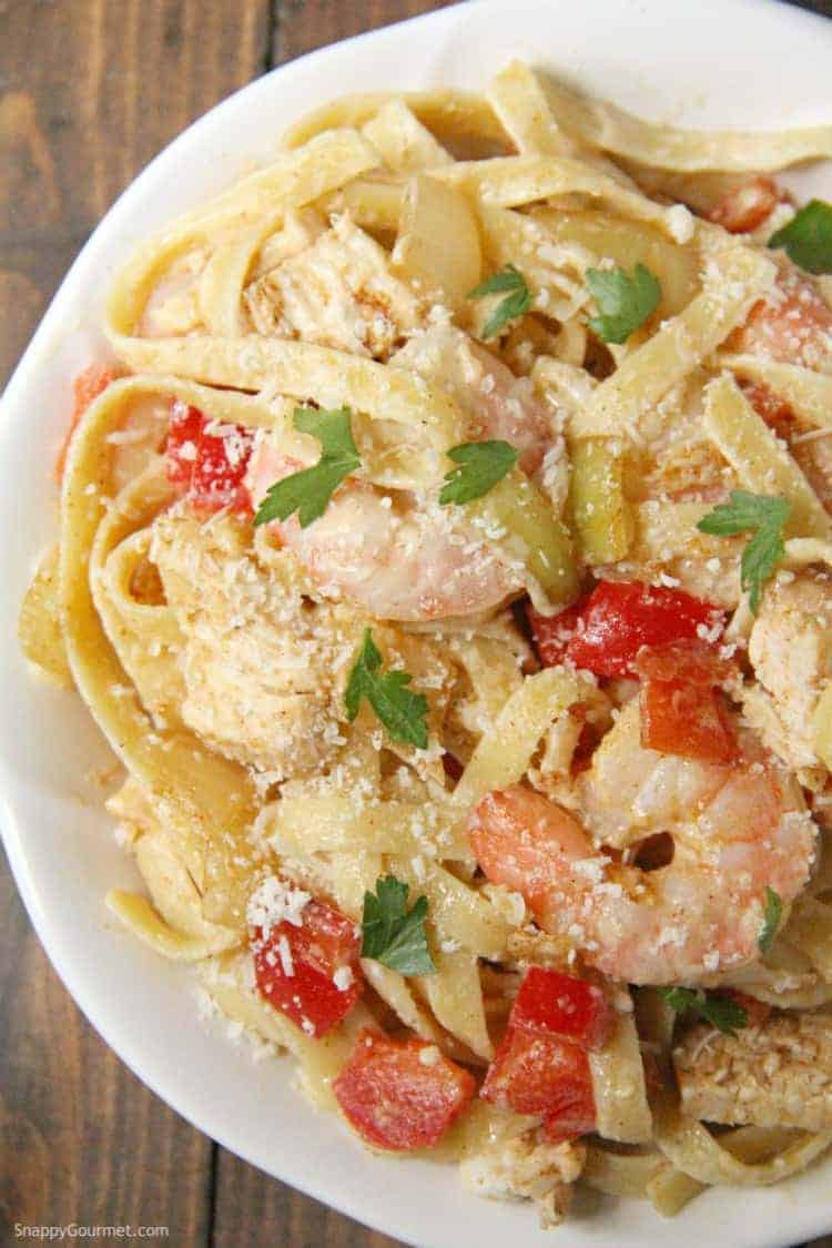 delicious Cajun Chicken and Shrimp Alfredo Pasta on plate with peppers and onions