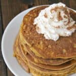 stacked pumpkin pancakes with whipped cream
