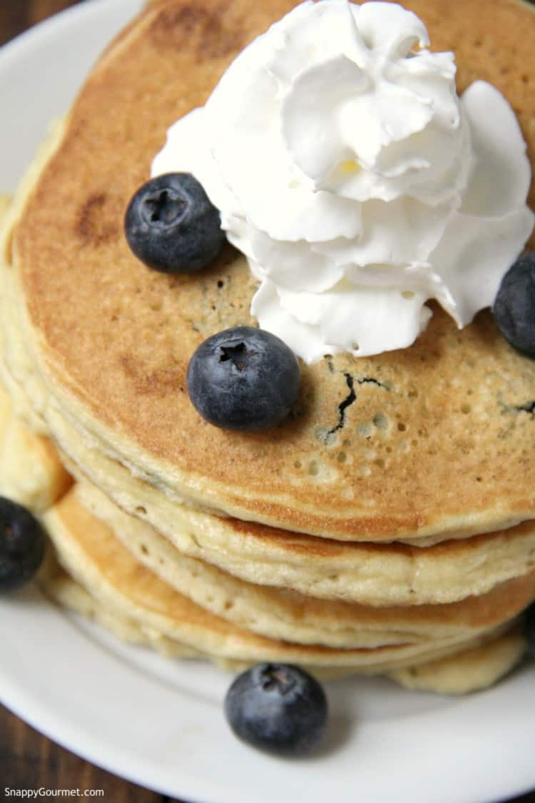 almond flour blueberry pancakes on plate with blueberries and whipped cream