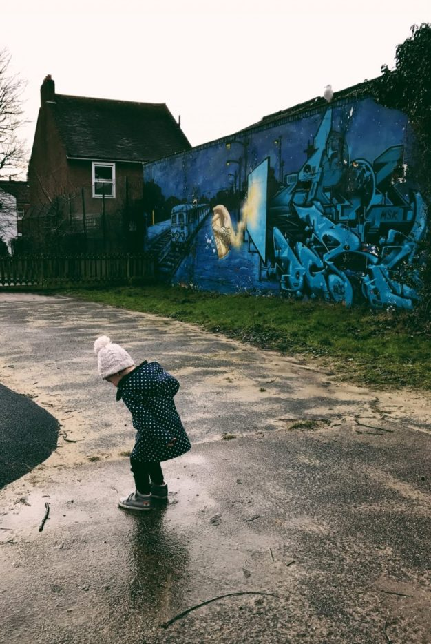 toddler girl jumping puddles