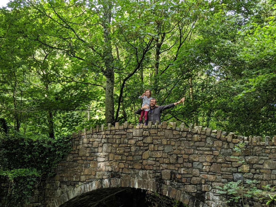 child and male adult on stone bridge over river heddon with green trees in background