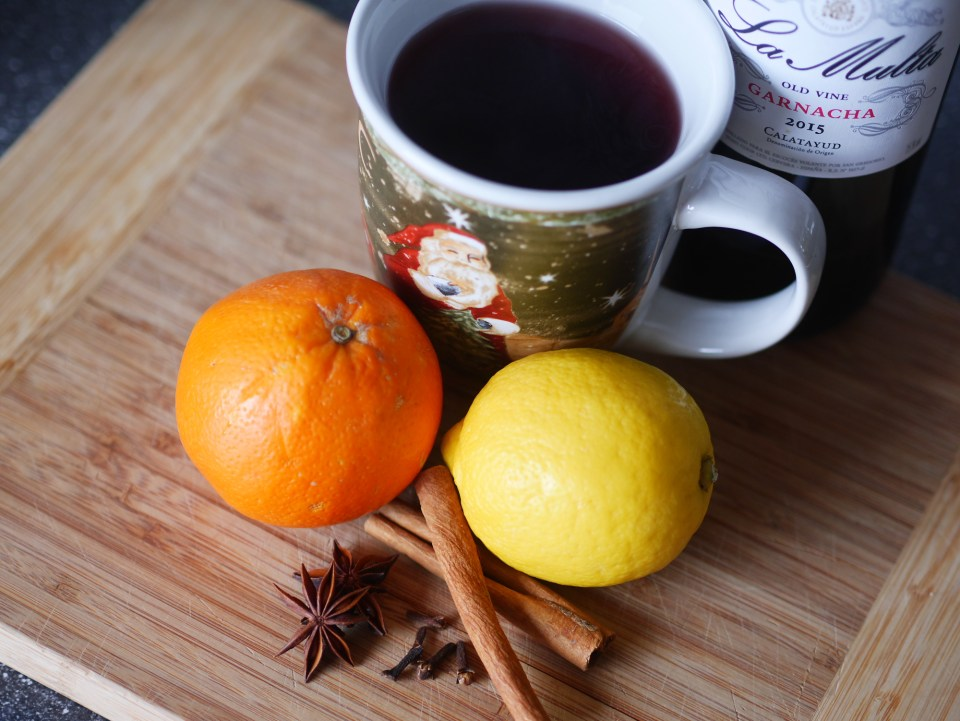 ingredients for mulled wine, including wine, cloves, lemon, orange, cinnamon and star anise