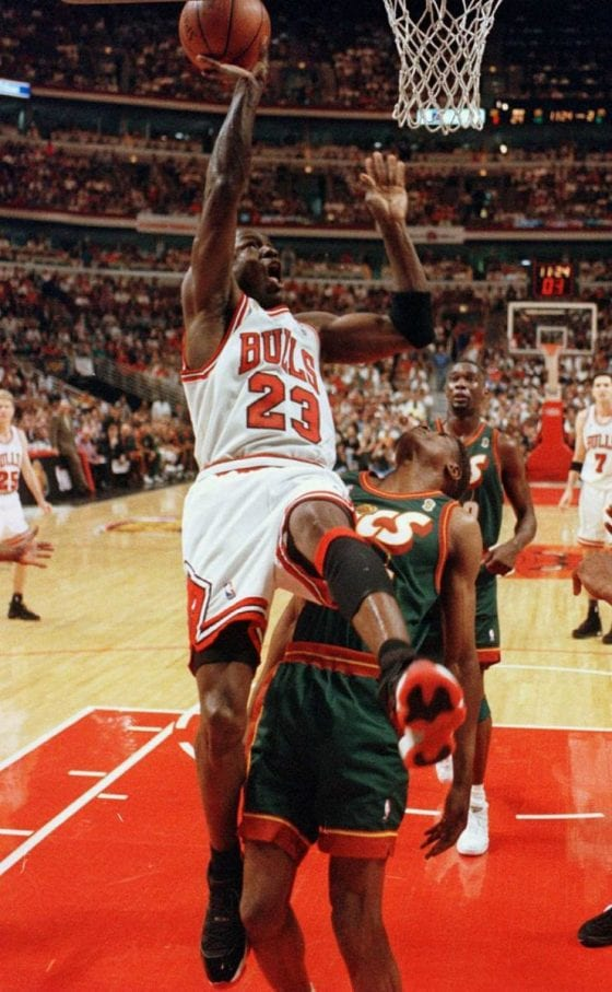 Michael Jordan of the Bulls,wearing the Jordan XI 'Playoff' shooting a lay-up while being fouled by David Wingate of the Sonics Image via Solecollector