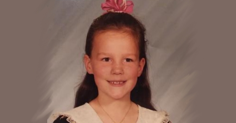 A school photo of Erica when she was about eight years old. She is smiling peacefully, with a hint of mild concern behind her eyes. She has a hair bow on top of her head, her long hair is pulled back, her little dress has some sort of laced shawl attached to it in that 1990s little girl fashion they used to have.