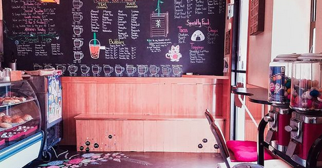 Photo taken from intrinsic cafe's instagram, it is of the entrance of the cafe, looking at the giant chalk board with all of their menu items written on it, with cute illustrations. There is also a bench and evidence of a refrigerated pastry display cabinet that they do business over.