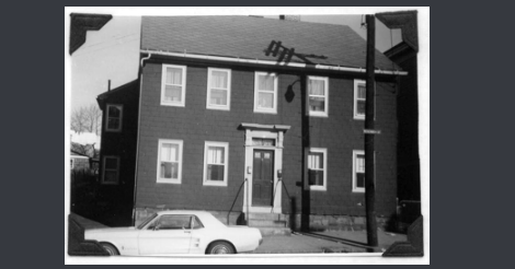 This is an old black and white photo of the original building. It looks to be painted a darker color.
