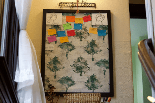 """We see a little bulletin board with rectangles of different colors pinned to it. There is a basket and some things under it. It looks like little drawings of Dollissa and Amandoll are in the corners. Above it is a silly little thing that says """"you got this."""""""
