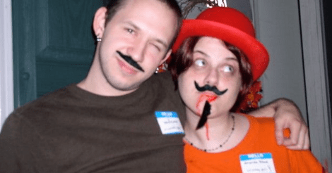 An old almost-blurry photo of a guy and a gal -- Kevin and Amandoll. They both have various amounts of fake facial hair on, and name tags. Amandoll has fake blood streaming from her mouth and a matching red hat.