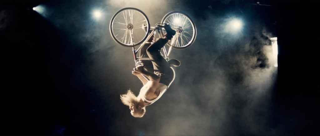 Fahrradartist Jacques Schneider in Aktion - er ganz normal auf dem Fahrrad sitzend, aber in der Luft, 180° gedreht, Kopf nach unten.