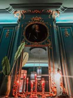 Dekoration auf dem Kaminsims im hinteren Barbereich - Kerzen auf dem Sims, Spiegel, Pflanze und Portrait über dem Spiegel.
