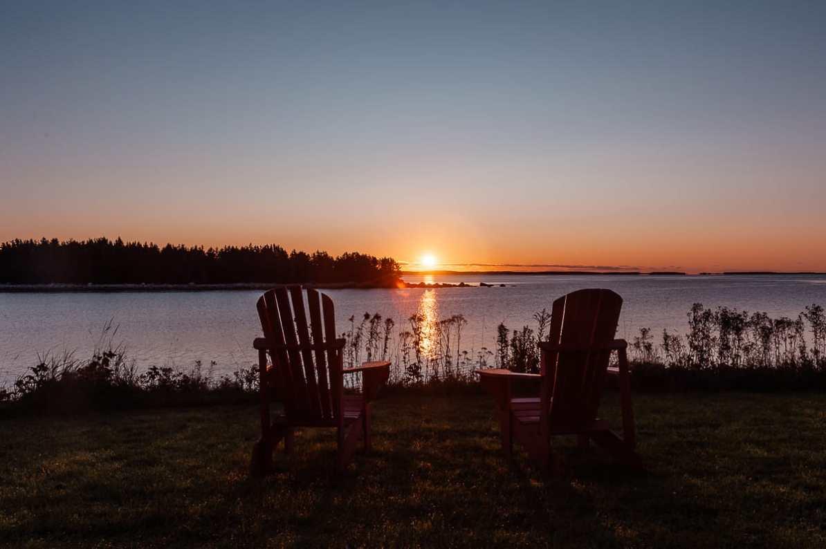 East Shores Nova Scotia, Sonnenaufgang über dem Wasser, direkt an einer Insel, zwei typisch kanadische Deckchairs im Vordergrund.